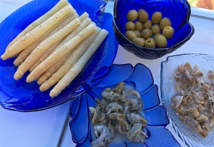 Plates of white asparagus, sea snails and clams conservas