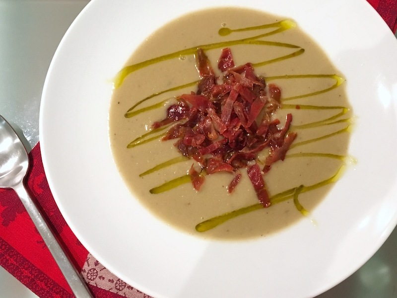 Creamy artichoke soup garnished with serrano ham